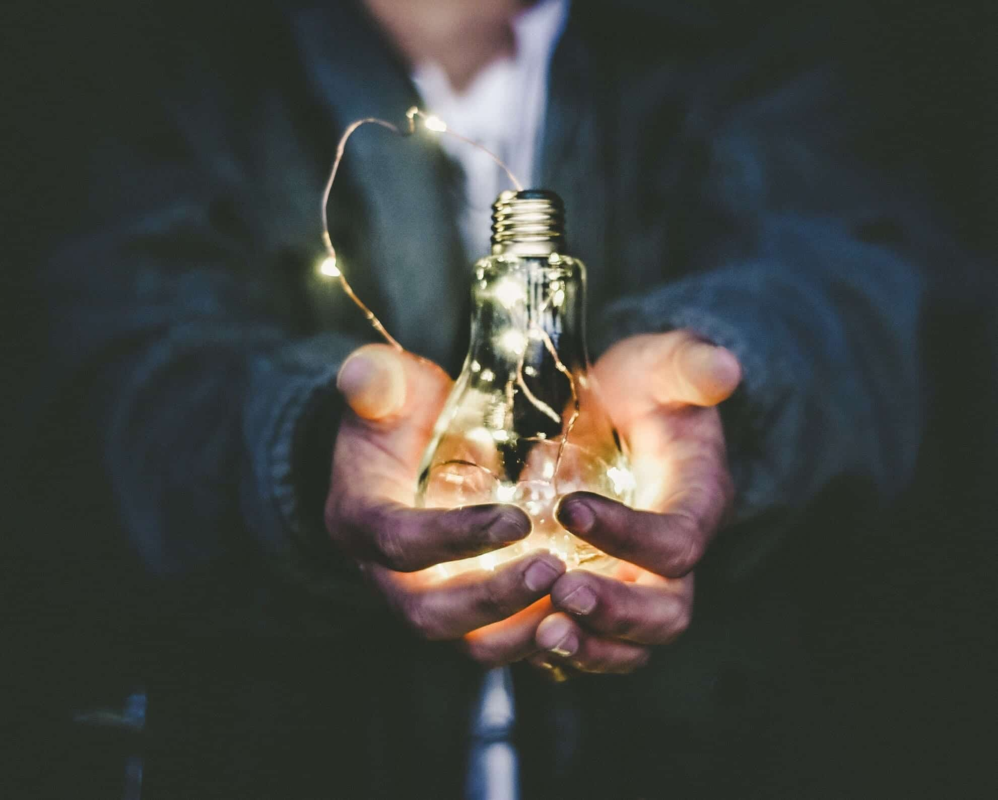 Man holding incandescent light bulb; image by Riccardo Annandale, via Unsplash.com.