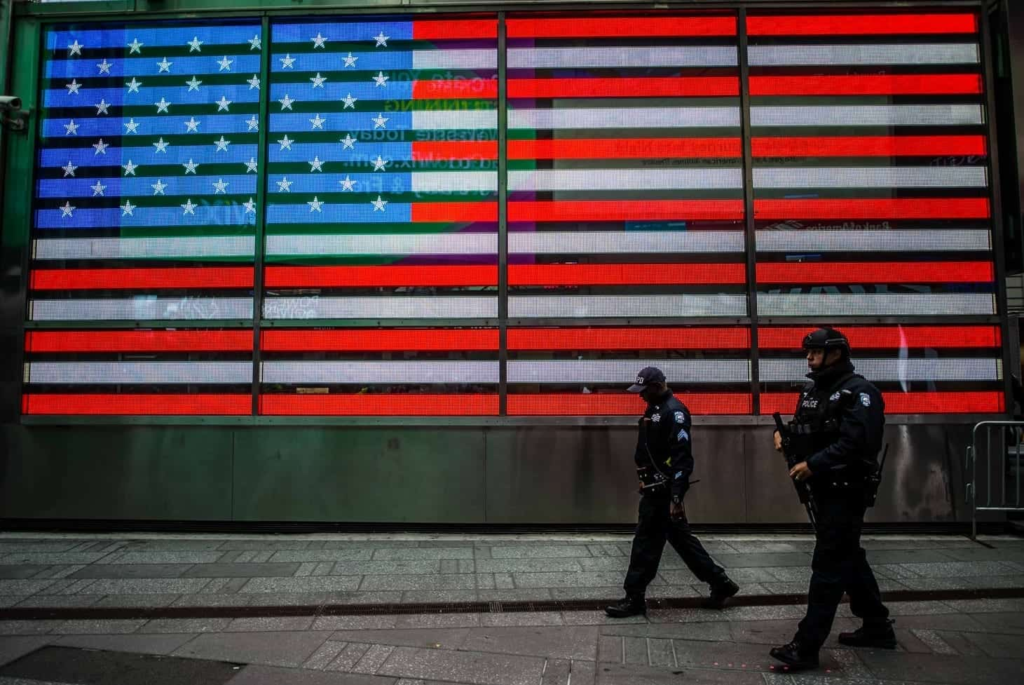 Two NYPD officers walk in front of an American Flag mural.