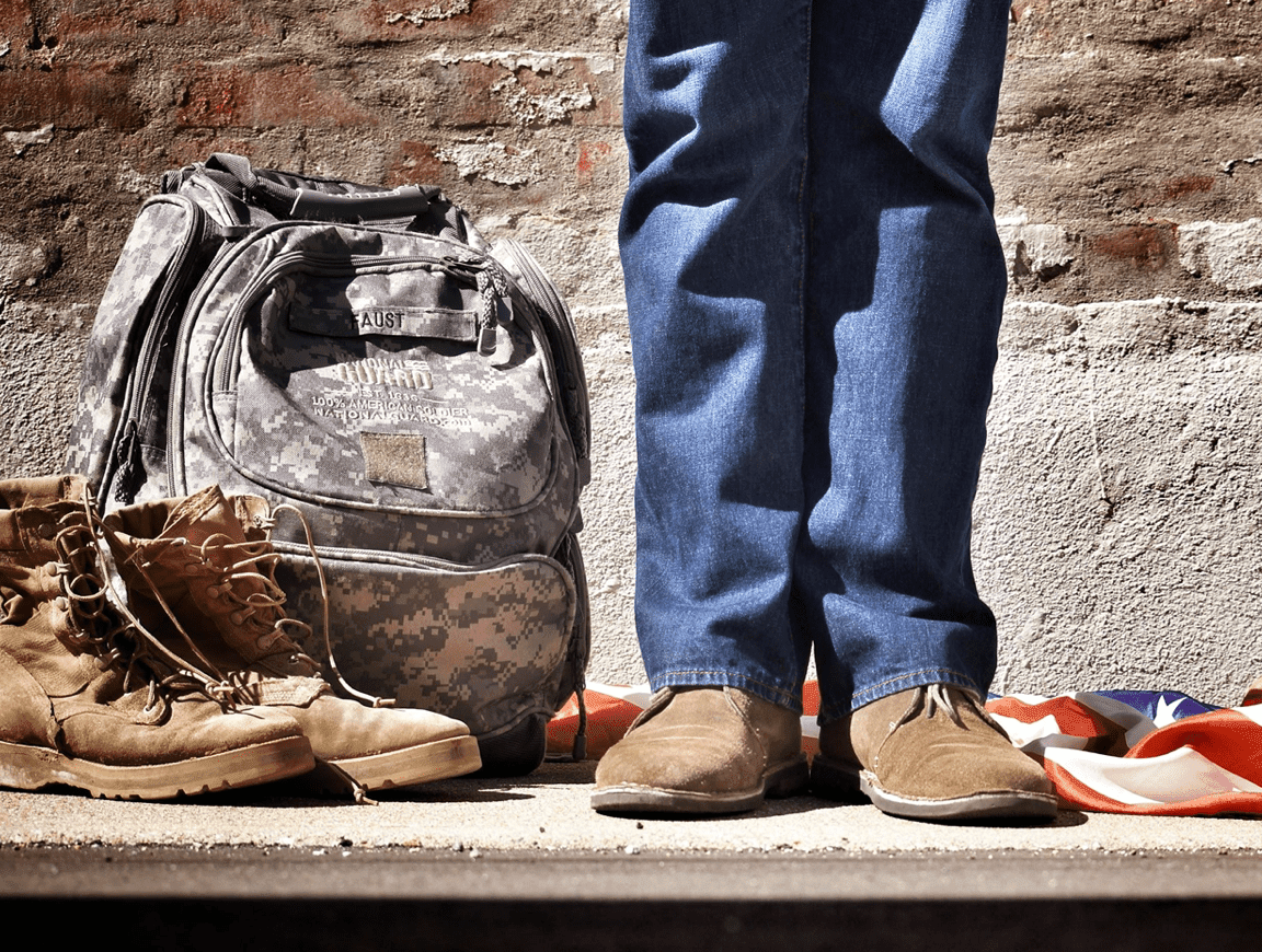 Veteran in blue jeans standing by military backpack, boots, and an American Flag; image by Benjamin Faust, via Unsplash.com.
