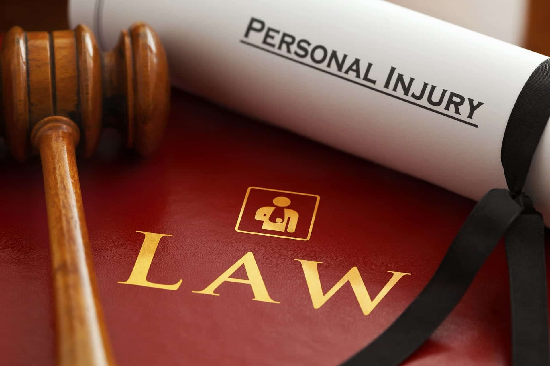 """Gavel and rolled paper with """"Personal Injury"""" on it sitting on top of dark red binder titled """"Law."""" Image by Claimaccident, via pixabay.com. No changes."""