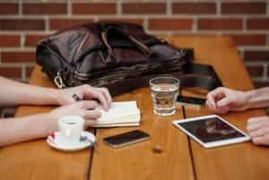 Two people meeting with iphone and ipad; image by Alejandro Escamilla, via Unsplash.com.