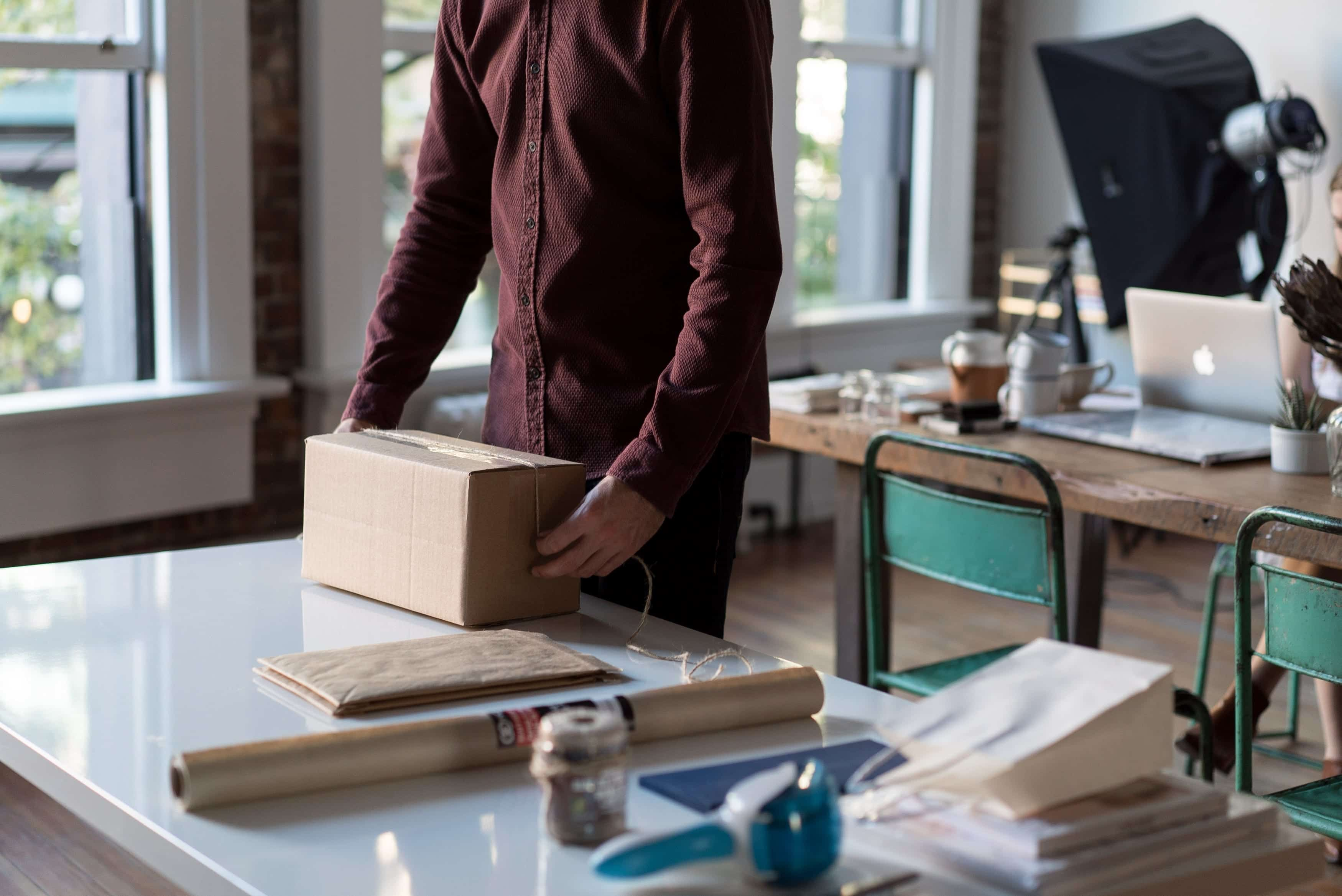 Man in maroon shirt packing a box in the office; image by Bench Accounting, via Unsplash.com.