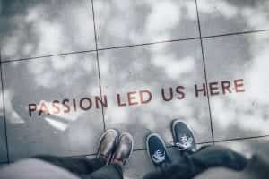 "Two people standing on grey tile paving with ""Passion Led Us Here"" printed at their feet; image by Ian Schneider, via Unsplash.com."