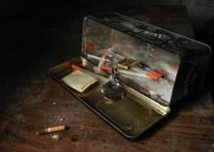 Clear and red syringes inside open tin can near cigarette butt; image by Matthew T. Rader, via Unsplash.com.