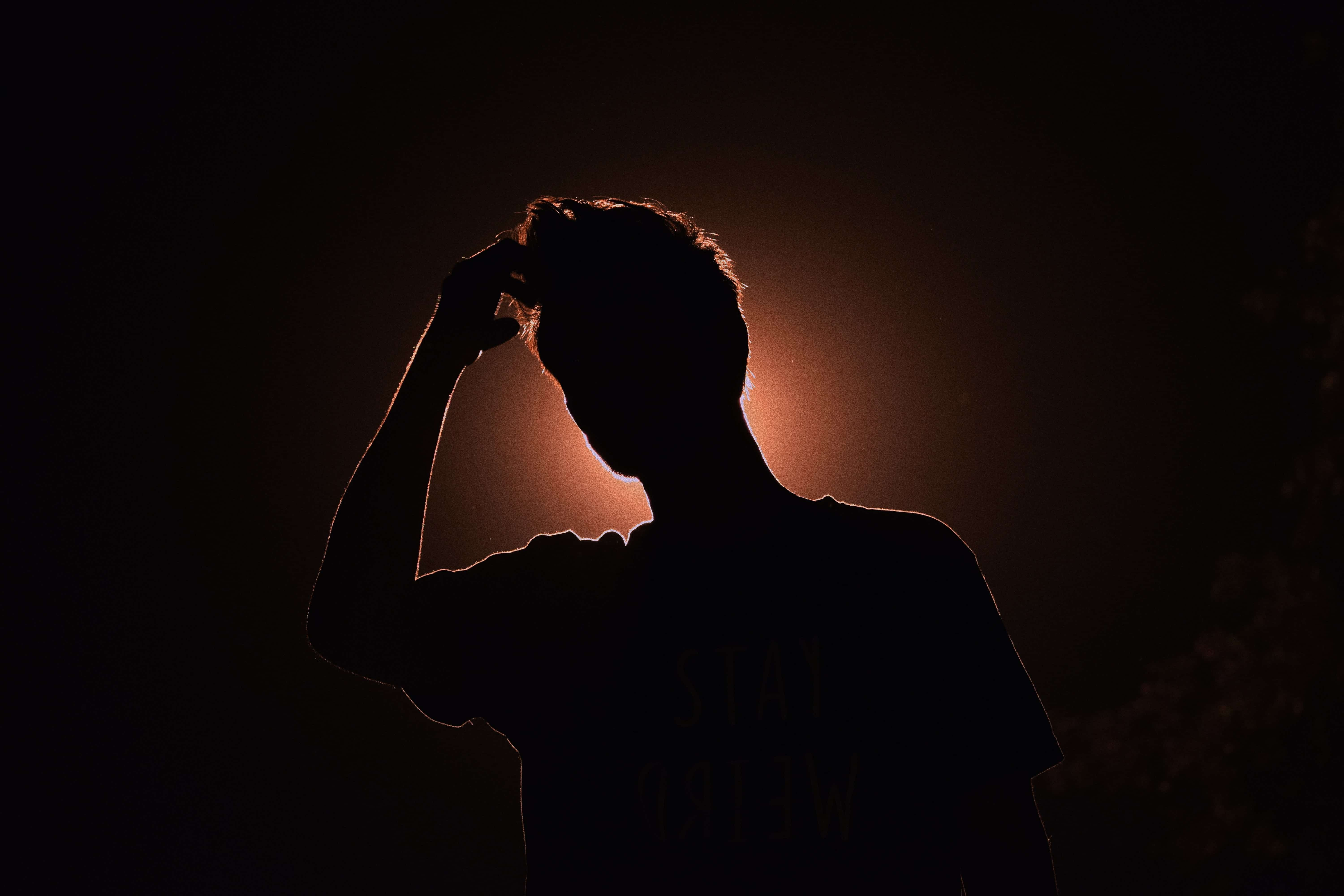 Silhouette image of man touching his head; image by Smit Patel, via Unsplash.com.