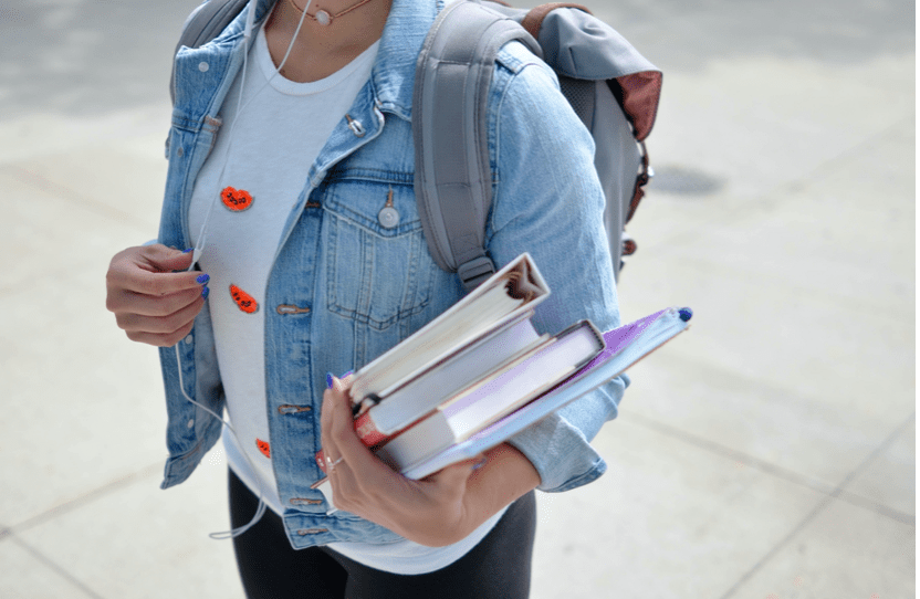 Young female student carrying books, binders, and a backpack; image by Element5 Digital, via Unsplash.com.