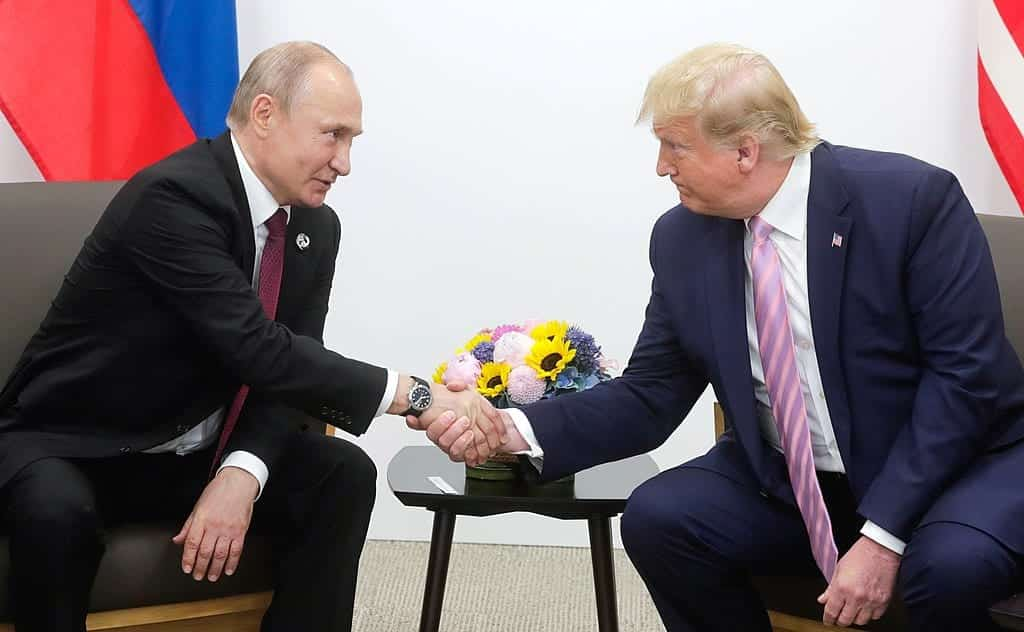 President Trump and Russian President Putin, seated, shaking hands.