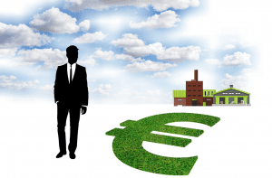 Graphic of man in suit against blue sky with white clouds. Factory in background; money sign with green grass fill in foreground. Image by Tumisu, via Pixabay.com.